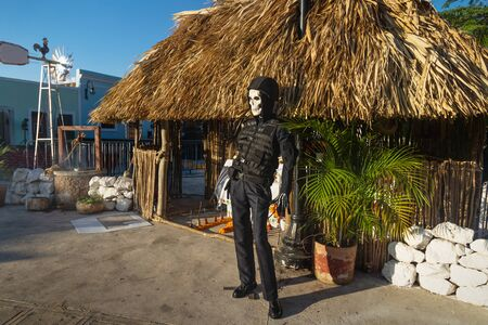 Puppet with skull mask and police uniform in front of altar for celebration of 'dia de los muertos' day of the dead, Merida, Yucatan, Mexico