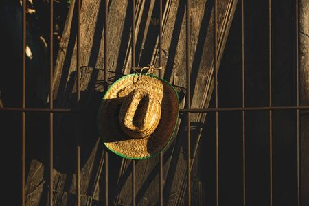Mexican straw hat with green border on sunlit dark brown wooden fence