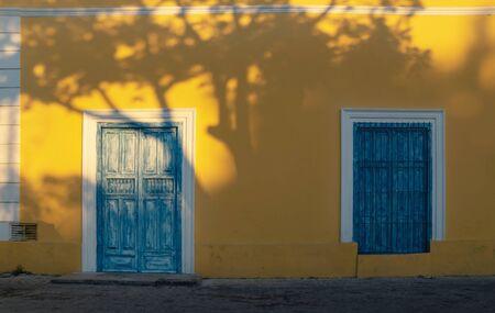 Sunlit facade of colorful colonial building with blue door and beautiful tree shadows in Merida, Yucatan, Mexico