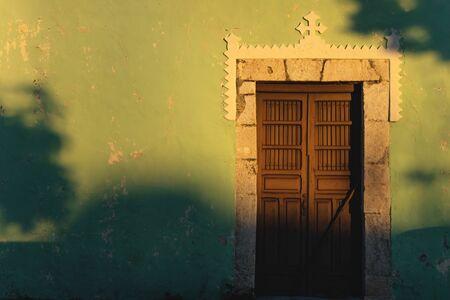 Sunlit facade of colorful colonial door with cros and beautiful shadows in Merida, Yucatan, Mexico