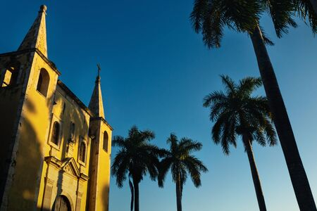Santa Ana church facade framed by palm trees during sunset light, and cloudless blue sky Merida, Yucatan, Mexico