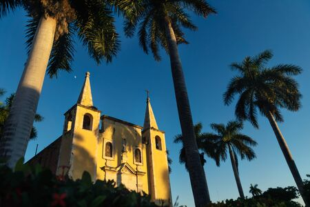 Front of Santa Ana church framed by palm trees during sunset light, and cloudless blue sky Merida, Yucatan, Mexico Stock Photo