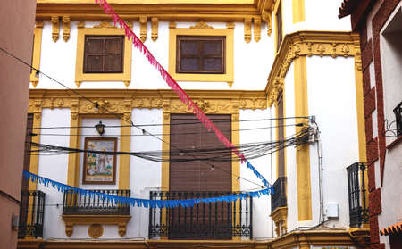 Historic house facade with yellow stucco and tile painting of Siant Francesco Assisi and colorful flags in Polop de Marina, Spain