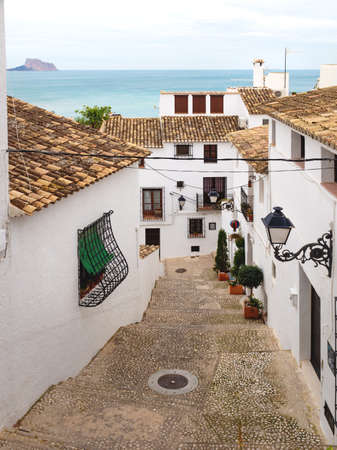 Steps in narrow street with white washed houses and view over the ocean and the rock of Calpe in the old town of Altea, Costa Blanca, Spain