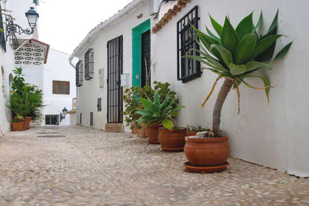 Alley with flower pots along the white washed houses in the old town of Altea, Costa Blanca, Spain Archivio Fotografico