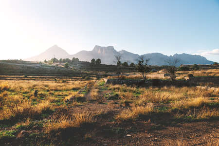 Dry former farmland on the countryside of Costa Blanca during sunset with lit mountains, La Nucia, Spain