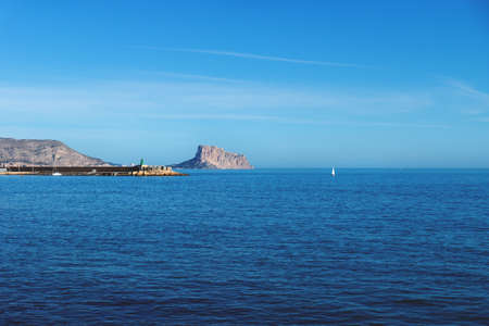 Panoramic view over the deep blue ocean to the rock of Calpe with sailboat, Costa Blanca, Spain Stock Photo