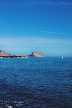 Panoramic view over the deep blue ocean to the rock of Calpe and port of Altea, Costa Blanca, Spain Stock Photo