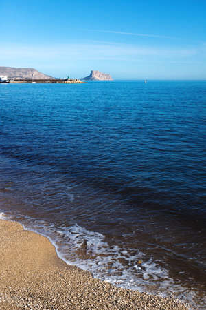 Beach view over the deep blue ocean to the rock of Calpe, Costa Blanca, Spain Stock Photo
