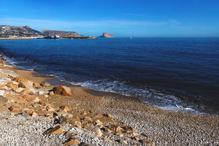 Panoramic view over the deep blue ocean to the rock of Calpe along stone coast, Costa Blanca, Spain Stock Photo