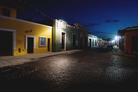 Traditional domnestic Mexican street with colonial buildings and small white flags in the night, Merida, Yucatan, Mexico