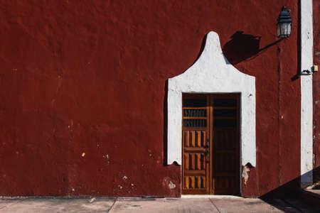 Dark red Colonial building with wooden door, Valladolid, Yucatan, Mexico
