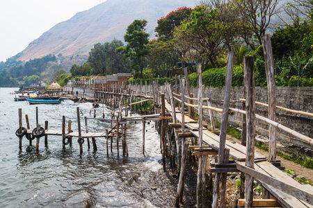 Narrow wooden bridge and docks along lake Atitlan and steep mountain at the coast of Santa Cruz la Laguna, Guatemala Stock Photo