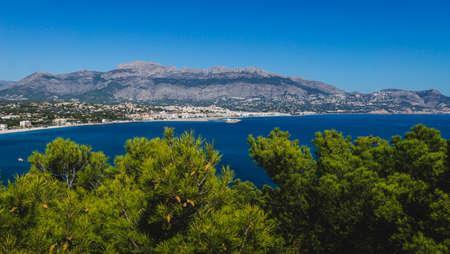 Panoramic coastal view to Atea over mediteranean sea and blurred pines in natural park 'Serra Gelada' in Albir, Costa Blanca, Spain