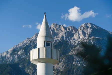 Minaret tower of a mosque in front of sunny rocky Austrian alps in Telfs, Tirol, Austria