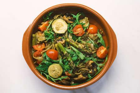 Seasonal vegan mediterranean Italian pasta pot with fried asparagus, zucchine, tomato, champigon and arugula