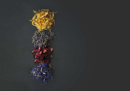 Top view of floral herbs - dried marigold, lavender, rose and cornflower petals as aromatic ingredients for cooking or tea Stock Photo
