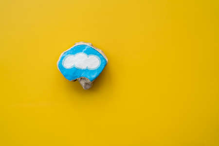 Painted stone with blue bordered cloud on yellow background as symbol for handcraft hobby and happiness