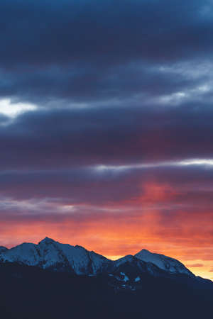Alpine mountains with snow tops at sunset with dramatic red purple colored stormy cloudscape in Tirol, Austria Stock Photo