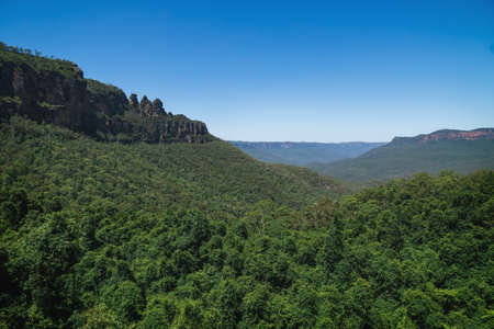 View into green forest valley with the rock formation 'Three Sisters' in the Blue Mountains, Katoomba, New South Wales, Australia