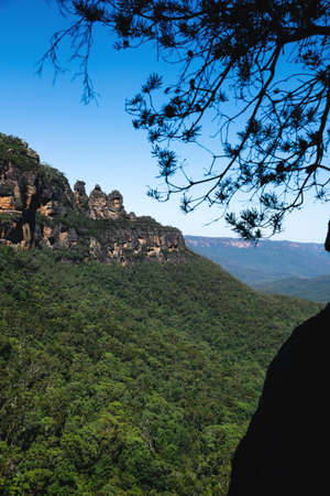 View into green forest valley and cliffs with the rock formation 'Three Sisters' in the Blue Mountains, Katoomba, New South Wales, Australia