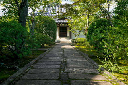 Kyoto, Japan - September 18, 2017: Path surrounded by trees to temple building in Sogenchi garden at Tenryu-ji