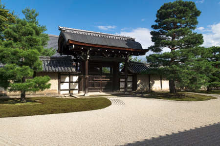 Kyoto, Japan - September 18, 2017: Sunlit stone zen garden with typical pattern with raked gravel an gate at Sogenchi garden at Tenryu-ji temple Editorial