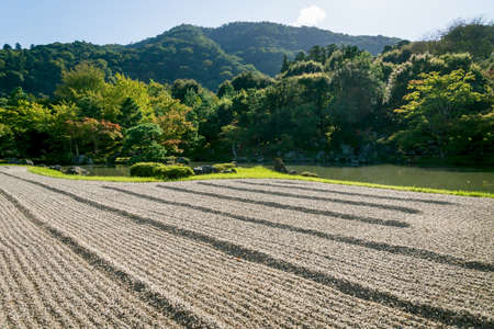 Kyoto, Japan - September 18, 2017: Stone zen garden with with raked gravel along pond at Sogenchi garden at Tenryu-ji temple with mountains in background Editorial