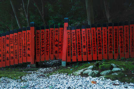 Red fence with japanese text along forest and moss covered stones at Mikami-jinja Shrine in Kyoto, Japan Stock Photo