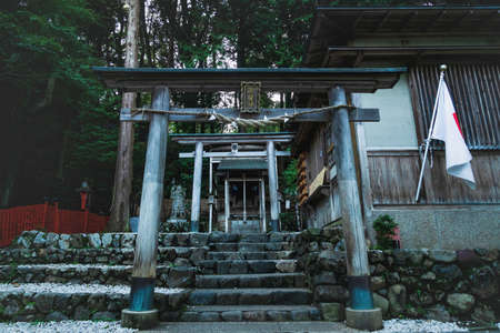 Entrance to temple with torii gates at Mikami-jinja Shrine sorrounded by forest in Kyoto, Japan