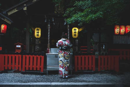Kyoto, Japan - September 18, 2017: Woman in traditional kimono praying at Nonomiya Shrine in the evening Editorial