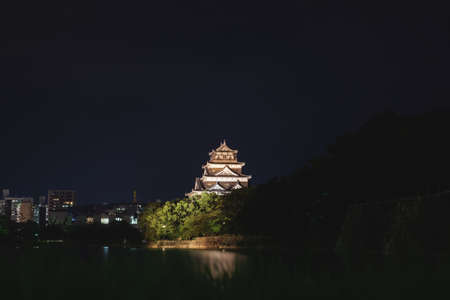 Hiroshima, Japan - September 15, 2017: The illuminated Hiroshima castle, also called Carp Castle, surrounded by water with reflections in the cityscape at night