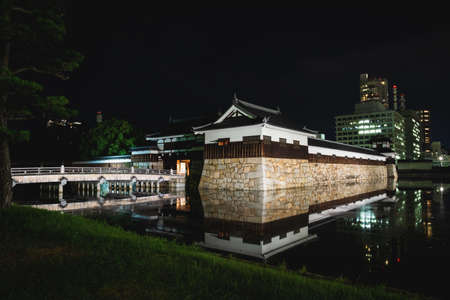 Hiroshima, Japan - September 15, 2017: The illuminated Hiroshima castle, also called Carp Castle, with bridge surrounded by water with reflections in the night Editorial