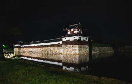 Hiroshima, Japan - September 15, 2017: The illuminated fortress walls of Hiroshima castle, also called Carp Castle, surrounded by water with reflections in the night