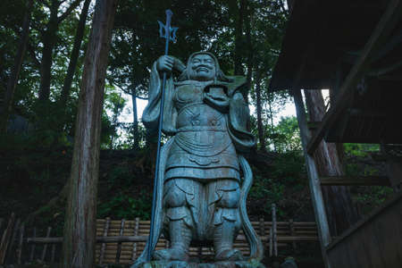 Kyoto, Japan - September 18, 2017: Samurai statue from low angle view as a guardian of the Mikami-jinja Shrine