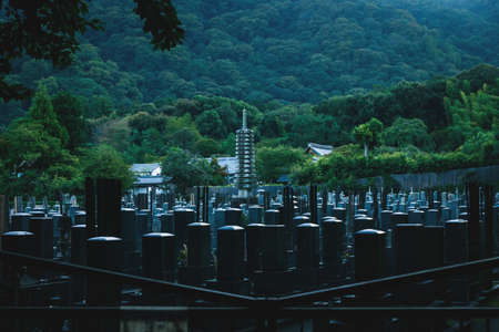 Kyoto, Japan - September 18, 2017: Dark moody view on the Tenryu-ji Temple Cemetery along forest covered mountains during blue hour