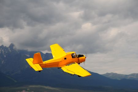 airborne vehicle: Yellow aircraft on display at an airshow.- aerial dusting