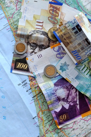 paper money and coins on the map of israel photo