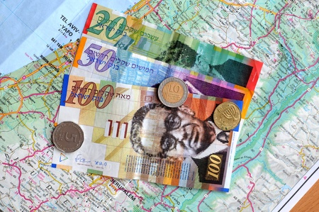 paper money and coins on the map of israel