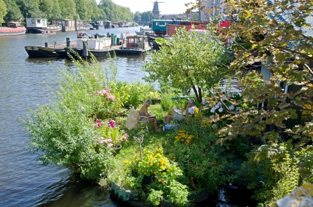 Amsterdam Holland August Beautiful Dutch flower garden with Dutch pensioners on a canal. (Amsterdam)