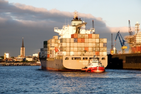 Hamburg Germany september 2013:Containership in port of Hamburg container ship with red tugboa Editorial