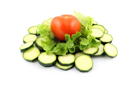 details of a fresh zucchini and tomato isolated on white on salad