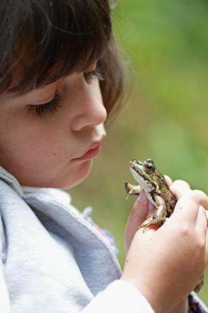 detalles de una rana en las manos de una ni�a Foto de archivo