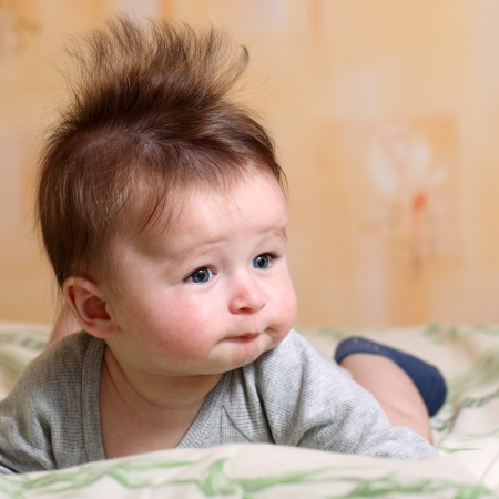 Portrait of a baby 4 months old lying on his belly with mohawk hairstyle