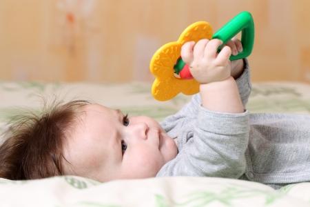 Retrato de un beb� jugando acostado sobre la espalda Foto de archivo