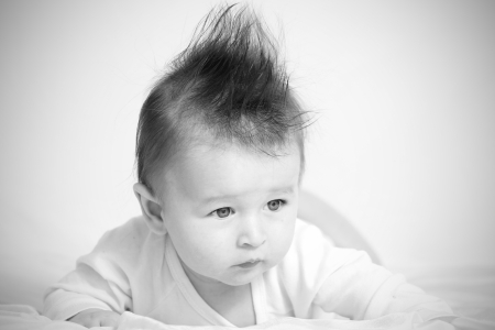 baby hairstyle: Portrait of a baby 4 months old lying on his belly with mohawk hairstyle.