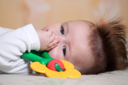 baby hairstyle: Portrait of a baby 4 months old lying down with mohawk hairstyle. Stock Photo