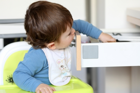 Details of a little boy who is trying to catch a knife in a drawer in kitchen  Stock Photo