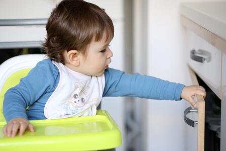 Detalles de un ni�o peque�o que est� tratando de abrir un caj�n de la cocina. Foto de archivo