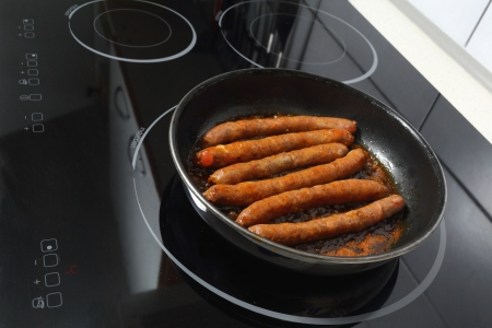 Details of merguez sausages baking in a frying pan on ceramic hob. photo